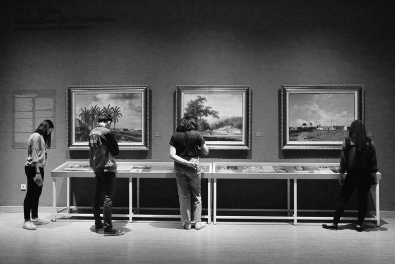 TOEIC Part1|3人以上の人がギャラリーで絵画を見ている写真
